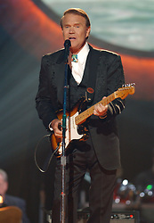 """08 August 2017 - Various - Glen Campbell, the voice behind 21 Top 40 hits including """"Rhinestone Cowboy,"""" """"Wichita Lineman"""" and """"By the Time I Get to Phoenix,"""" died Tuesday. He was 81. During a career that spanned six decades, Campbell sold over 45 million records. In 1968, he outsold the Beatles. Campbell was married four times, and has five sons and three daughters. In the early 1980s, while battling alcoholism and cocaine addiction, Campbell made tabloid headlines with a 15-month, high-profile relationship with country singer Tanya Tucker, who was 22 years his junior. In 1981, he became a born-again Christian and in 1982 he married Kimberly Woollen, a Radio City Music Hall Rockette. In 2003, he was arrested for a hit-and-run, an incident that ended with him allegedly kneeing a police officer in the thigh right before he was released. Campbell pleaded guilty to extreme drunken driving and leaving the scene of an accident, and spent 10 days in jail. In 2011, Campbell, then 75, revealed that he was diagnosed with Alzheimer's disease. In June of that year, he announced he was retiring from music due to the disease. He released his final album of original music Ghost and embarked on a farewell tour with three of his children backing him. File Photo: Jun 04, 2003; Nashville, TN, USA; Singer GLEN CAMPBELL performing at CMT's 100 Greatest Songs of Country Music held at the Gaylord Entertainment Center. Photo Credit: Photo: Laura Farr/AdMedia *** Please Use Credit from Credit Field ***"""
