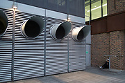 Taking a cigarette break outside large air vents outside an office building in London, England, United Kingdom.
