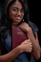 Portrait of young hispanic woman holding bible in black background.