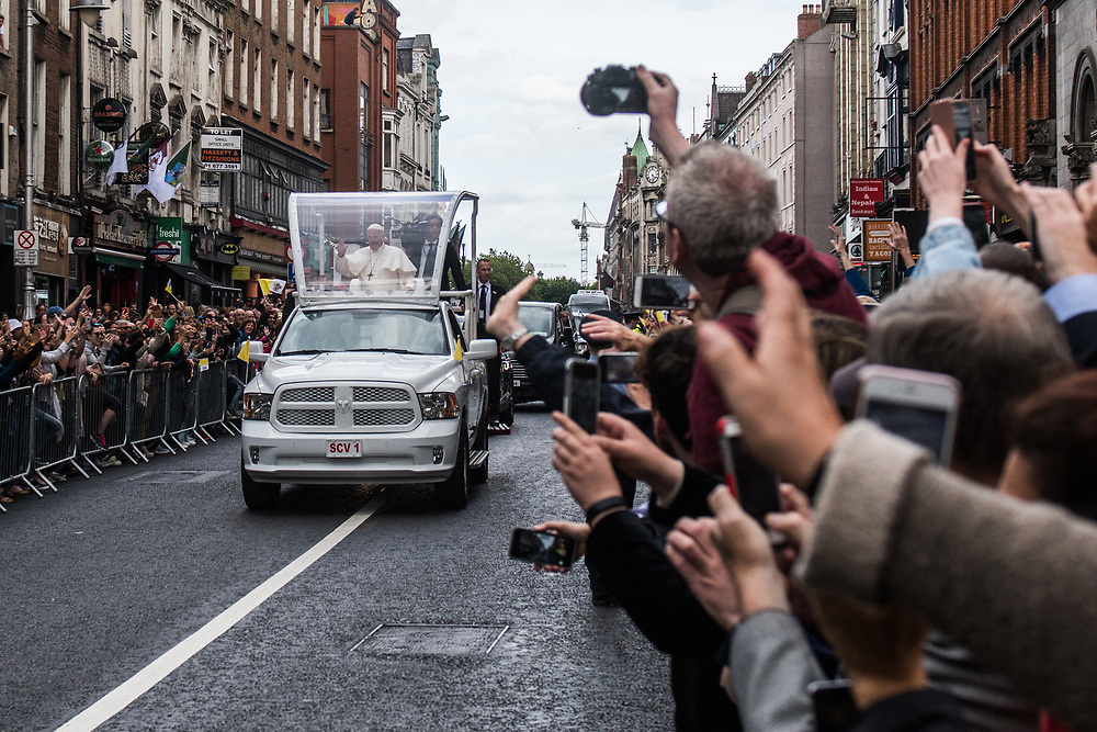 """Dublin, Ireland. 25th August, 2018. <br /> Pope Francis passes in his pope-mobile along Parliament Street in the afternoon during the first of the two-days of his visit in Dublin, Ireland.<br /> Pope Francis has made a two-day visit to the Republic of Ireland by celebrating a Mass at Dublin's Phoenix Park. The Argentine Pope asked forgiveness for the """"abuses in Ireland, abuses of power, conscience and sexual abuses"""" perpetrated by Church leaders. It was the first papal visit to Ireland for 39 years. During his activities many activists, victims and survivors have made protests and a silent march Garden of Remembrance towards the last Magdalene Laundry to close in Ireland.<br />  © Simone Padovani"""