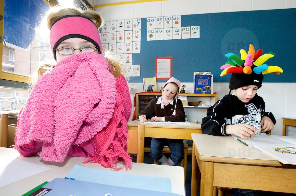 """Nederland Maassluis 16 februari 2007 .Warme truiendag in Zuid Holland, kinderen met muts, sjaal en handschoenen aan tijdens een les in het klaslokaal op Montessorischool om energie te besparen. Op de dag van de ratificatie van het Kyotoprotocol zetten 60 scholen de kachel een paar graden lager of zelfs helemaal uit en kwamen leerlingen warm aangekleed naar school..In heel Zuid Holland zijn scholen gevraagd mee te doen aan de """"warme truiendag"""" op vrijdag 16 februari. Dit idee komt van de Raad voor het Klimaat en wordt ondersteund door de provincie Zuid Holland. Zij willen jongeren laten meedenken over wat gemeenten en provincie kunnen doen aan het klimaatbeleid. Daarom vragen zij de basisscholen in heel Zuid-Holland de verwarming op warme truiendag een paar graden lager te zetten en de kinderen aan te sporen met een dikke trui naar school te komen. De warme truiendag is inmiddels geadopteerd door het Klimaatverbond; zij willen de Warme truiendag volgend jaar landelijk gaan organiseren. Op school TV wordt er aandacht besteed aan de actie. Als een school meedoet aan de klimaatquiz krijgen ze als beloning voor deelname een wachtwoord waarmee ze de Ali B clip kunnen downloaden. Ali B vraagt de leerlingen een foto te maken van de klas in warme trui en die op te sturen. De winnaar verdient een optreden van Ali B op hun school..In Maassluis doen de Montessorischool en basisschool De Dijck mee aan de warme truiendag. .Foto David Rozing"""