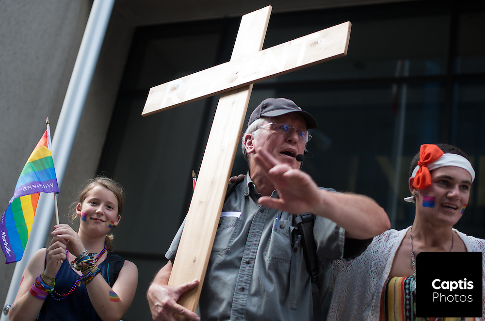 Parade participants stand beside a man urging them to repent. August 24, 2014.
