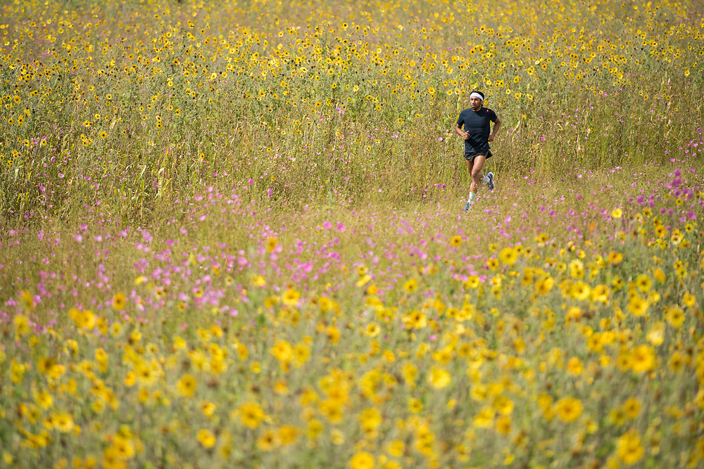 Crisanto Grajales running on a field with flowers  in Hidalgo, Mexico.<br /> Client: Red Bull