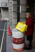 A lady with a Selfridges department store shopping bags stands by old construction oil drum outside Ritz roadworks.