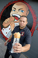 Chef John Collazo stands next to a mural outside his Bad As's Sandwich shop, which is located in the area known as the Milk District in Orlando, Fla., Saturday, March 25, 2017. (Phelan M. Ebenhack via AP)