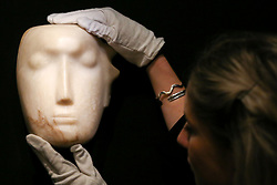 "© Licensed to London News Pictures. 12/11/2018. London, UK. A member of staff holds ""The Man Behind the Mask"", a Henry Moore's masterpiece (British, 1898-1986). (Estimate: £1,000,000-1,500,000). The work is one of 12 known, small carvings by Moore titled Mask, and, uniquely, is the only one carved from alabaster.<br /> Bonhams Modern British and Irish Art photocall. Auction to be held on 14 November 2018. Photo credit: Dinendra Haria/LNP"