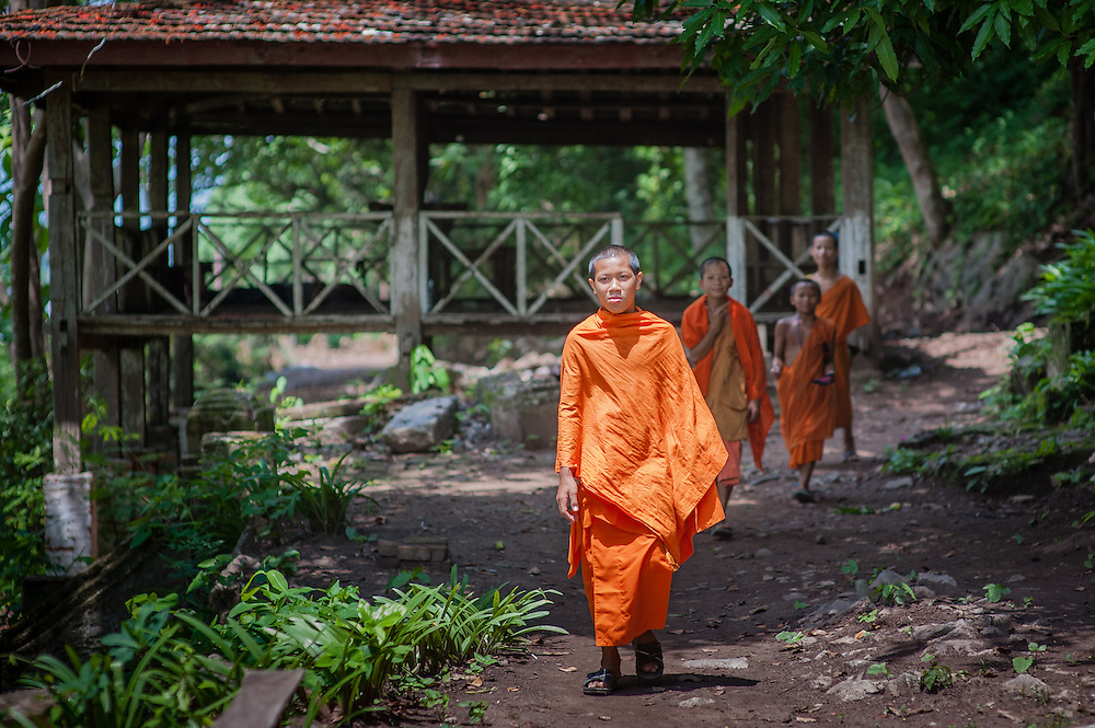 The bright #orange color of #Buddhist monks in Laos and Cambodia make them very visible anywhere they go. When the background is green, like in this image, and the sun is lighting up the robes, to me monks seem like walking flames. #travelphotography #Laos