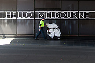 """A worker wearing a mask pushes a large trolley under a """"Hello Melbourne"""" sign during COVID-19 in Melbourne, Australia. Premier Daniel Andrews announced today that some minor changes will be made to the current Stage 4 Restrictions in Melbourne. As yet, there is no sign of any meaningful change despite numbers of new cases being under 5 for the 14 day rolling average. Zero cases and no deaths were recorded in the past 24 hours in Victoria. (Photo by Dave Hewison/Speed Media)"""