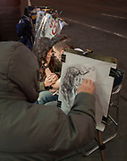 A couple in tender caress in a world of their own is captured in pencil by a street artist.