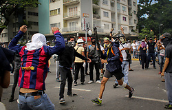 A demonstrator steals weapons from the National Guard during a protest against Venezuelan President Nicolás Maduro in Caracas on May 3, 2017.