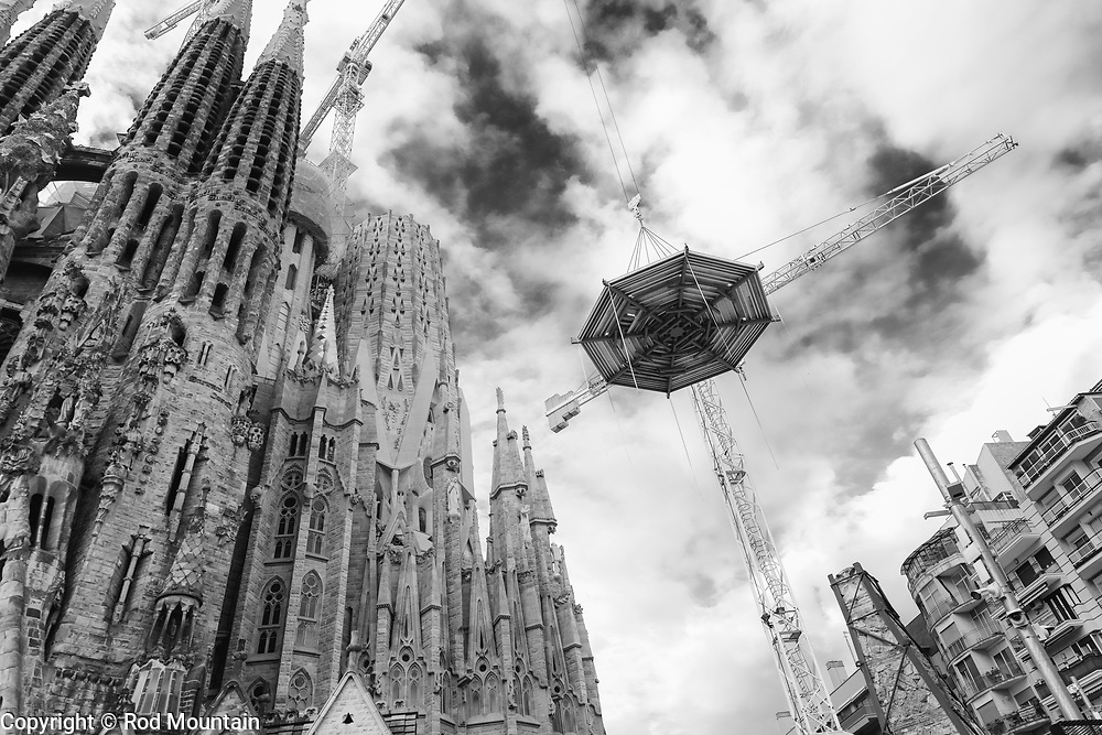 """Barcelona, Spain - February 20, 2018 - The historic construction continues at the Temple Explatori de la Sagrada Familia in Barcelona, Spain. The ground breaking took place in 1882 and the structural work and decorations continue to this day. The designer of this amazing UNESCO World Heritage Site is Catalan architect Antoni Gaudi (1852-1926). On the subject of the extremely long construction period, Gaudi once remarked; """"My client is not in a hurry.""""<br /> <br /> Image: © Rod Mountain http://www.rodmountain.com<br /> <br /> @spain @barcelona_cat @visitbarcelona @basilicasagradafamilia <br /> <br /> @spain.info @bcn.cat @BasilicadelaSagradaFamilia @visitbarcelona<br /> <br /> @spain @barcelona_cat @sagradafamilia @VisitBCN_EN<br /> <br /> https://sagradafamilia.org<br /> https://en.wikipedia.org/wiki/Sagrada_Fam%C3%ADlia<br /> https://www.barcelona.cat/en/<br /> https://www.barcelonaturisme.com/wv3/en/<br /> https://www.spain.info/en/<br /> <br /> #documentary #europetravels #europetrip #TourismSpain #natgeo #travelworld #Fodorsonthego #bw_perfect #bnw_barcelona #nb #bnw_planet #bnw_guru #noireetblanc #bnw_awards #bnw_diamond #lensculturestreets #createexplore #bnw_demand #lookingup #architectonics_world #gaudiarchitecture #gaudi #VisitSpain #Barcelona"""