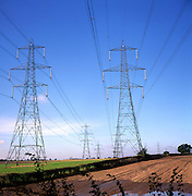 Pylons carrying high voltage electricity cables cross countryside