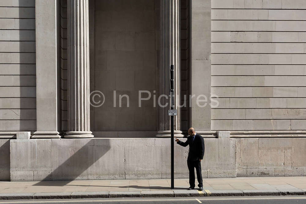 A business man walks beneath the high outer walls of the Bank of England in the City of London, the capitals financial district, on 25th March 2019, in London, England.