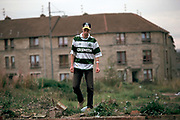 A young Celtic fan walks through a housing estate in Glasgow wearing a replica shirt of his favourire team, Celtic FC. Celtic have a strong following of mostly Irish Catholics and are bitter rivals to the city's other team, Glasgow Rangers.