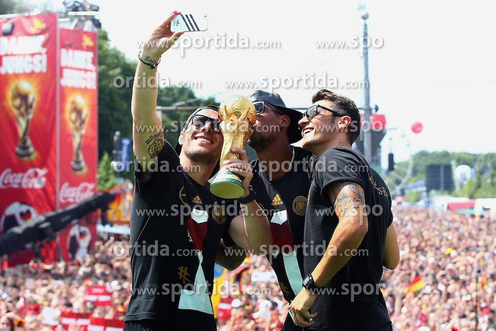 15.07.2014, Brandenburger Tor, Berlin, GER, FIFA WM, Empfang der Weltmeister in Deutschland, Finale, im Bild vl. Lukas Podolski (GER), Jerome Boateng (GER) und Mesut Oezil (GER) // during Celebration of Team Germany for Champion of the FIFA Worldcup Brazil 2014 at the Brandenburger Tor in Berlin, Germany on 2014/07/15. EXPA Pictures © 2014, PhotoCredit: EXPA/ Eibner-Pressefoto/ Pool<br /> <br /> *****ATTENTION - OUT of GER*****