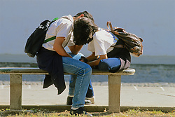 Two Teenagers Kissing In Park