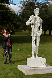 """© Licensed to London News Pictures. 07/10/2020. LONDON, UK. A woman views """"Untitled 1 (Bodybuilders)"""", 2015, by David Altmejd at Frieze Sculpture, an annual exhibition of outdoor works by international artists in Regent's Park.  The works are on display to the public until 18 October.  Photo credit: Stephen Chung/LNP"""