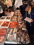 An official with a clipboard checks the quality of seafood on sale on at  Tsukiji Wholesale fish market n Tokyo, Japan. September 14th 2005