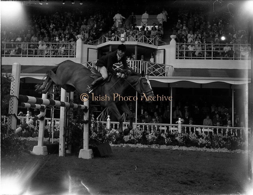 """04/08/1960<br /> 08/04/1960<br /> 04 August 1960<br /> R.D.S Horse Show Dublin (Thursday). Captain the Honourable John Brooke riding """"Tyrenny"""" owned by the Honorable Mrs Brooke, clearing a pole jump in the International Jumping Competition for the Boylan Memorial Perpetual Challenge Trophy at the Dublin Horse Show."""
