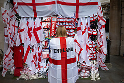 © Licensed to London News Pictures. 10/07/2021. LONDON, UK.  A woman buys an England flags in Piccadilly Circus ahead of the final of Euro 2020 between Italy and England tomorrow night Wembley Stadium.  It is the first major final that England will have played in since winning the World Cup in 1966 but Italy remain unbeaten in their last 33 matches.  Photo credit: Stephen Chung/LNP