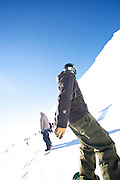 A snowboarder weaves through traffic on a trail at ski field Turoa. Turoa is located on active volcano Mount Ruapehu, New Zealand.