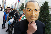 A man wearing a Steve Jobs mask stands in the lines of people at the Apple store awaiting the official release of the iphone4S in Ginza, Tokyo, Japan. Friday October 14th 2011. The latest version of the popular iphone was released worldwide on October 14th. Japans flagship Apple store in Ginza was opened at 8am for the 800 people that had been waiting to be the first to purchase the new telephone.