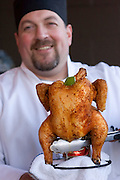 Bounty Hunter Restaurant, Napa, California. Napa Valley. Sous chef Paul Larsick with beer can chicken: smoked, steamed chicken barbecued on a can of Tecate beer.