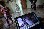A child plays in her house whilst her father looks at footage of the victims of a Syrian military attack on their village. The bodies of several residents were burnt after being killed. Basheria, Idlib, Syria. 14/06/2012