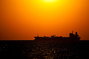Solar power or oil? Oil tanker at sunset, near Galveston, Texas in the Gulf of Mexico