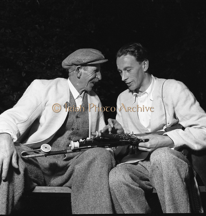 """Seamus Ennis (right) at Party at Iveagh Gardens - 1900 Period Dress<br /> 03/04/1957<br /> <br /> Séamus Ennis (05/05/1919 – 05/10/1982) was an Irish piper, singer and folk-song collector.<br /><br />In 1908 James Ennis, Séamus's father, was in a pawn-shop in London. Ennis bought a bag of small pieces of Uilleann pipes. They were made in the early nineteenth century by Coyne of Thomas Street in Dublin. James worked as a civil servant in Naul, Co Dublin. In 1912 he came first at the Oireachtas competition for warpipes, second at Uilleann pipes. He was also a prize-winning dancer. He married Mary McCabe in 1916. They had six children, including Séamus, who was born on May 5 1919 in Jamestown in Finglas, North County Dublin. James Ennis was a member of the Fingal trio, which included Frank O'Higgins (fiddle) and John Cawley (flute). They performed on the radio. At the age of thirteen, Séamus started receiving lessons on the pipes from his father. He attended the all-Irish schools at Scoil Cholm Cille and Colaiste Mhuire, which gave him a knowledge of the Irish language as well as English. He sat an exam to become Employment Exchange clerk but was too far down the list to be offered a job. He was twenty and unemployed.<br /><br />Colm Ó Lochlainn was editor of """"Irish Street Ballads"""" and a friend of the Ennis family. In 1938 Séamus confided in Colm that he intended to move to England to join the British Army. Colm immediately offered him a job at The Three Candles Press. There Séamus learned all aspects of the printing trade. This included writing down slow airs for printed scores - a skill which later proved important. Colm was director of an Irish language choir, An Claisceadal, which Séamus joined. In 1942, during The Emergency, shortages and rationing meant that things became difficult in the printing trade. Professor Seamus O Duilearge of the Irish Folklore Commission hired the 23-year old to collect songs. He was given """"pen, paper and pushbike"""" and a salary of thre"""