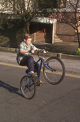 Young boy doing wheelies on bicycle in street,