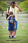 A father and his son salute a fallen soldier after placing a lei around the flag. Images taken at the National Cemetery of the Pacific in preparation for Memorial Day 2011.