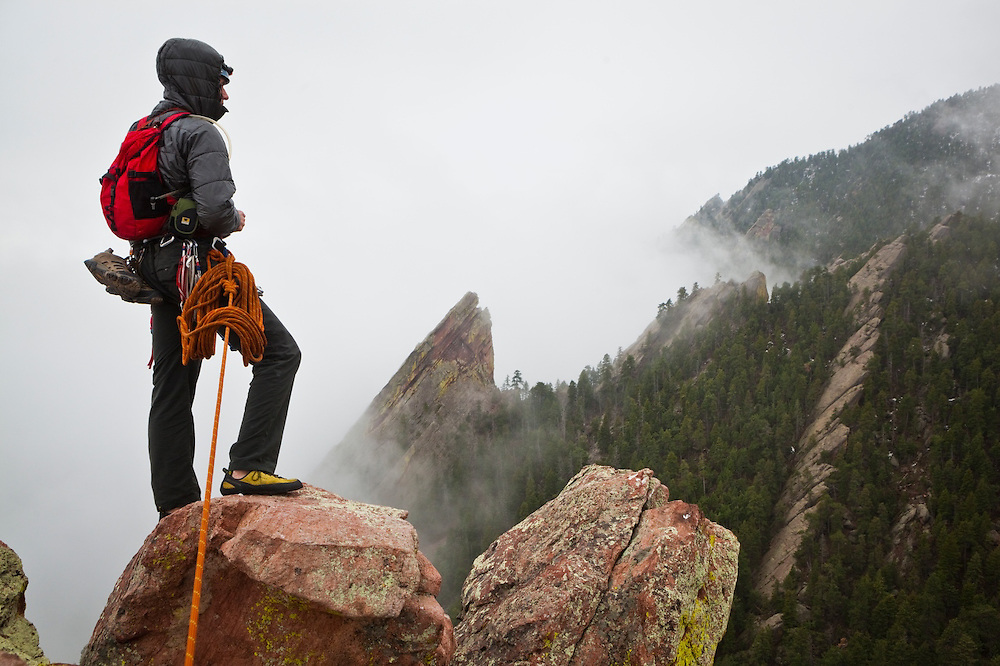 Obadiah Reid looks out towards the Third Flatiron from the summit of the First Flatiron above Boulder, Colorado, shrouded in mist.