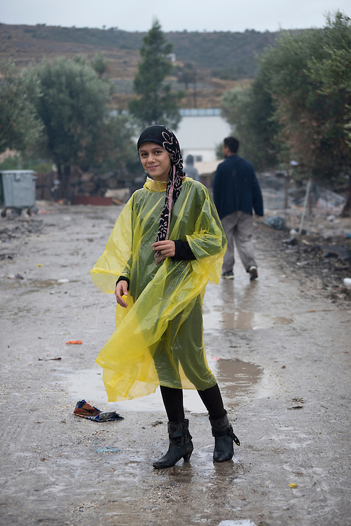 Rama, a 13-year-old girl from the Syrian city of Aleppo, stands on a dirt path at Kara Tepe camp near Mytilene, Lesbos, Greece. The camp was established for refugees transiting through Lesbos on their way from Turkey to the heart of Europe. Two other refugees are walking in the background.