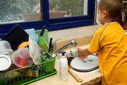A young boy of five works alone in the kitchen washes dishes Model release available