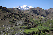 Snowy peak of Jebel Toubkal range foothills and crop fields in valley floor Atlas Mountains landscape, Morocco, north Africa