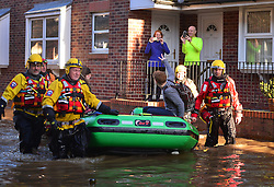 © Licensed to London News Pictures. 27/12/2015. York, UK.  A resident signals to others as he is evacuated by a mountain rescue team from a flooded street in York City centre. Large areas of the North of England have been hit by severe flooding following unusually heavy rainfall in December. Photo credit: Ben Cawthra/LNP
