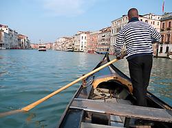 Oarsman ferrying passengers across Grand Canal in Venice by Traghetto public ferry gondola