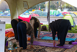 """A group practices Yoga in the """"wellbeing tent"""" as hundreds of environmental protesters from Extinction Rebellion occupy Marble Arch, camping in the square and even on the streets, blocking access to traffic on Park Lane and Oxford Street in London's usually traffic-heavy west end. . London, April 16 2019."""