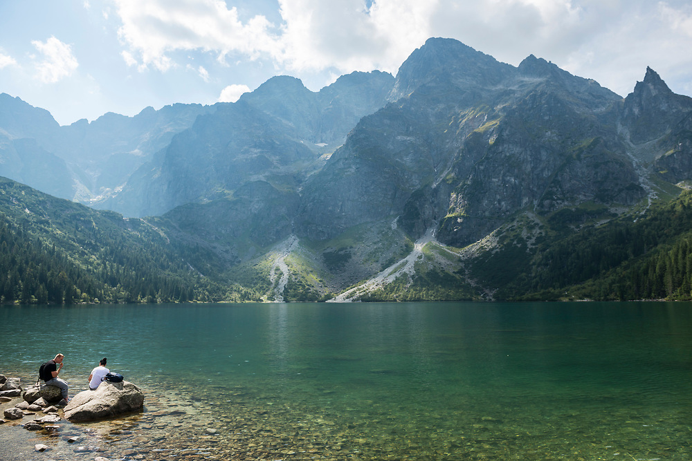 A man and woman sit beside the clear waters of Morskie Oko, a famous lake in southern Poland. Located within the Tatra National Park, Morskie Oko sits at an elevation of about 1400 meters above sea level.