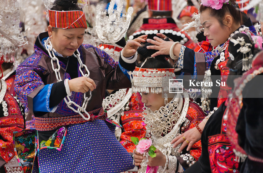 Miao ethnic womem helping young girls to dress in traditional costume at Sister's Meal Festival, Kaili, Guizhou Province, China