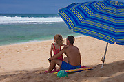 A little girl leans on her dad's shoulder as they look out to sea on the beach in Hawaii