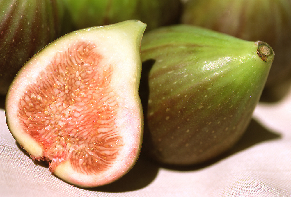 Close up selective focus photograph of some Brown Turkey Figs with one cut open to expose the fruit