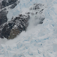 An avalanche crashes from a hanging glacier above Neko Harbor, Antarctica.