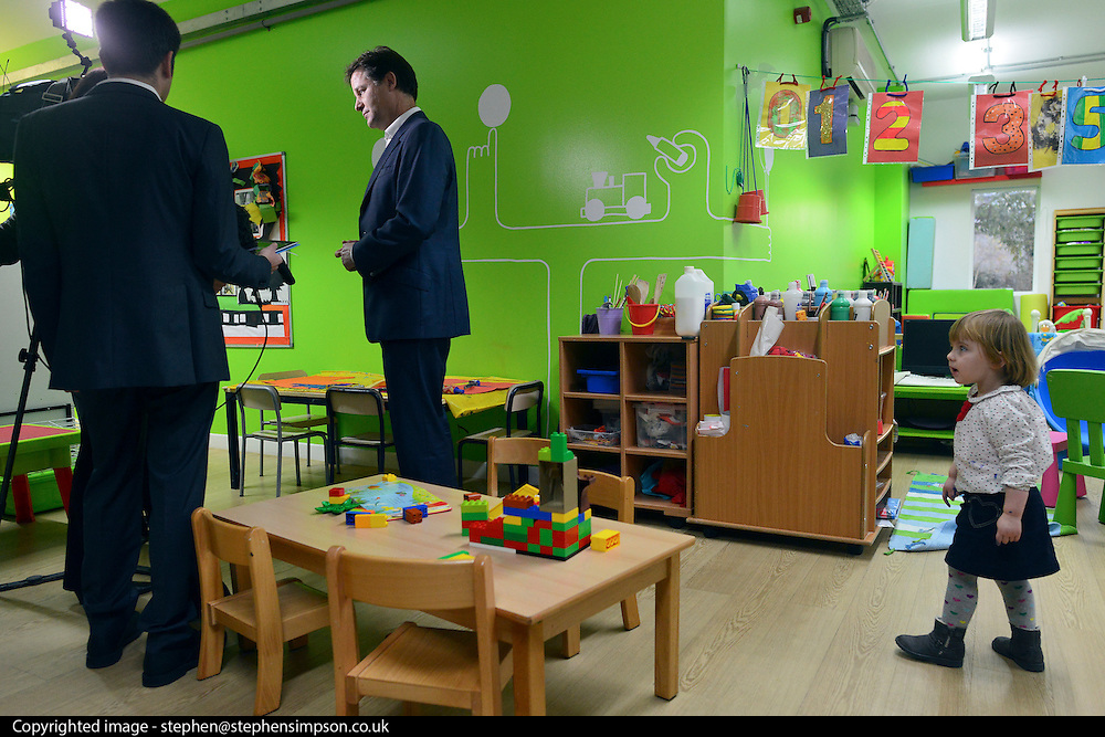 © Licensed to London News Pictures. 13/11/2012. London, UK Violet Stoodley aged two watches Nick Clegg conduct a TV interview. Deputy Prime Minister Nick Clegg visits the 'Third Door', in Putney today Putney today, 13 November 2012. An innovative centre combining a workspace for parents and childcare for their children, parents can drop off their children in the nursery, and hire a working space including desk, meeting room and facilities.  He announced new flexible parental leave for parents, mothers and fathers can now share the maternity leave allowance.. Photo credit : Stephen Simpson/LNP