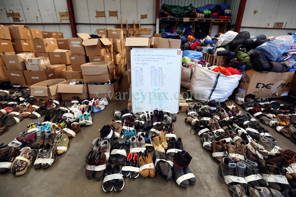 18 November 2020. Care4Calais - Calais, France.<br /> Care4Calais warehouse. Hundreds of pairs of shoes, all pre sorted and checked to ensure they are in good condition are laid out ready to be put into boxes for later distribution to desperate migrant refugees - many of whom have little more than flip-flops on their feet as winter approaches. <br /> Claire Moseley, founder of the British volunteer run refugee charity Care4Calais works tirelessly to build her foundation  to help migrant refugees as they struggle to survive on the streets of Calais where they are constantly harassed and moved on by authorities. Care4Calais provides meals, clothing, haircuts, charging stations for phones, medical aid, hot drinks, tents, blankets and a wide range of goods and services.<br /> Photo©; Charlie Varley/varleypix.com