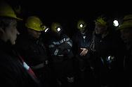 Minatori si ritrovano in una delle gallerie parlando dell'incerto futuro della loro azienda