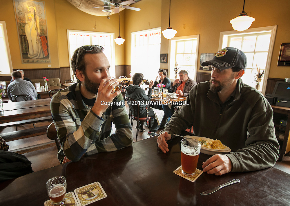 Todd Slater tries a beer while brewmaster Dave Griffiths eats lunch at LadyFace Ale Companie in Agoura Hills, CA. Shot Feb. 5th,  2013 Photo by David Sprague ©2013