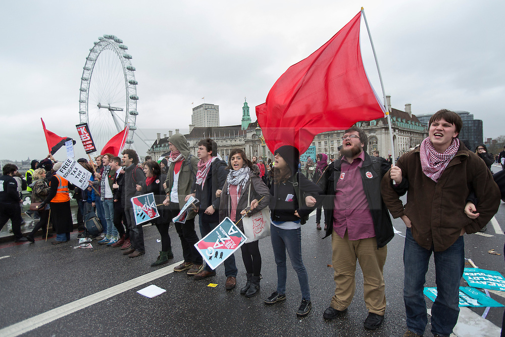 © licensed to London News Pictures. London, UK 21/11/2012. Students blocking the road on Westminster Bridge as students and members of the NUS (National Union of Students) march through central London to protest against government cuts to further and higher education, on November 21, 2012. Photo credit: Tolga Akmen/LNP