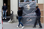 Art removal specialist workmen carry an artwork by the photographer Romina Ressia, into the Hofer Gallery in Maddox Street, on 30th April 2019, in London, England